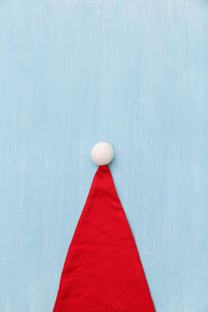 Top view of a red Santa Claus hat on a blue wooden table background. Free space for text. Festive, New Year and Christmas concept