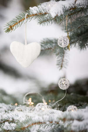 Knitted heart Christmas decoration on a snowy Evergreen tree outdoors. Winter, holidays season and Christmas concept. Traditional celebration.