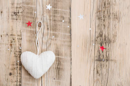 Top view on Knitted white heart Christmas decoration on old natural wooden table  with sparkling stars. New Year, holidays and celebration concept