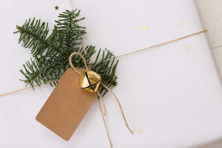 Top view on Christmas gift in white paper decorated with tree branch, tag and bell