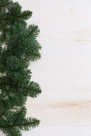 Top view with copy space on Christmas or New Year background: fur-tree on white wooden table. Holidays season.