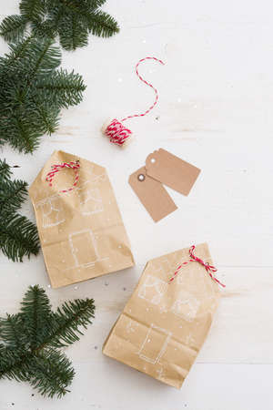 Top view on nice Christmas gifts package on white wooden table or background. Celebration, holiday season and winter concept