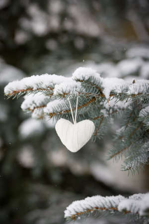 Closeup of beautiful knitted heart Christmas decoration on a evergreen tree with snow. Winter, Christmas celebration, holidays season concept 스톡 콘텐츠