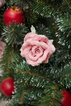 Colorful Christmas decorations on an evergreen tree. Handmade rose and red decorative apples on a Christmas tree. Winter, holiday concept 스톡 콘텐츠