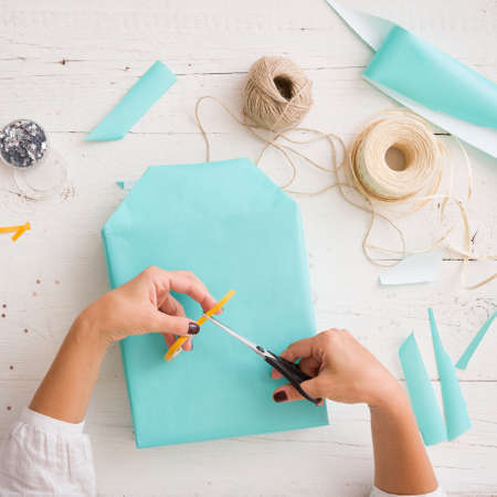 Close-up on a gift wrapped in paper of turquoise color. Hands of a young woman packing a gift on the background of a white wooden table. Preparations for the holiday. Accessories for packaging