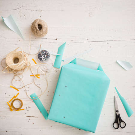 Close-up of a wrapped gift on a white wooden background. The gift is packed in turquoise paper. Ribbons, stars, twine, scissors lie on the table. Preparation for the holiday 스톡 콘텐츠