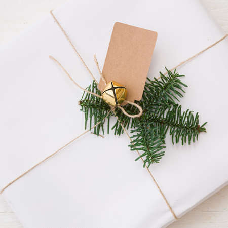 Closeup is a stylishly packed white box with a spruce branch, a tag and a bell tied with craft rope. Top view of a beautiful gift for Christmas and New Year. Holiday season and winter concept