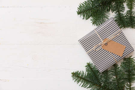 Gift box wrapped in paper and decorated with craft ribbon and tag. A gift for the New Year or Christmas on a white wooden table surrounded by fir branches. Christmas concept 스톡 콘텐츠