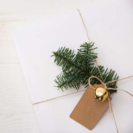 Closeup Christmas gift box wrapped in white paper and decorated with craft ribbon, bell, spruce twig and tag. A gift for the new year in on a white wooden table. Christmas concept 스톡 콘텐츠
