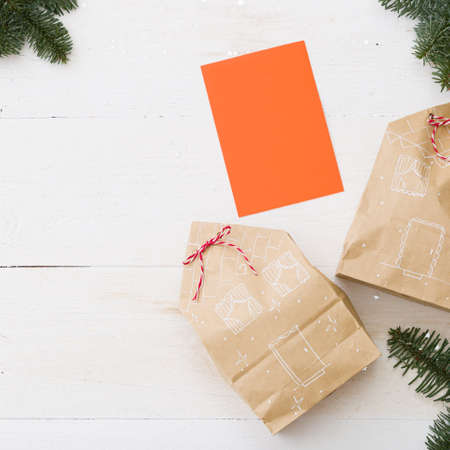 Closeup of stylishly packaged gifts in the form of houses tied with a rope, surrounded by fir branches. Top view of the beautiful gifts for Christmas and New Year. Blank orange greeting card for text.