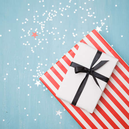 Top view of gifts lying on a blue wooden background. Stylish striped gift and a gift wrapped in white paper tied with a black ribbon. Silver stars are scattered on the table like confetti.