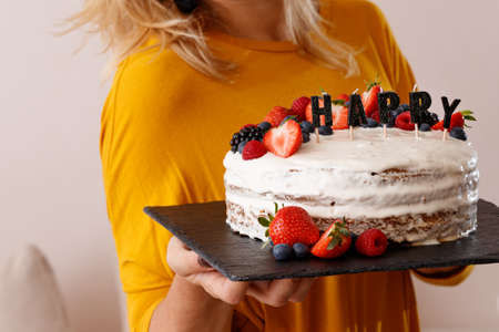 Closeup of a festive cake decorated with berries of strawberry, raspberry, blueberry. Candles the word happiness in the foreground. Layered cream cake on a black board in the hands of a young girl.