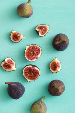 Top view of fig fruit scattered on a turquoise wooden table. Some figs are cut in half. 스톡 콘텐츠