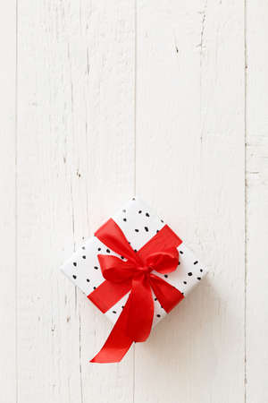 Closeup of a stylish birthday or christmas gift. White ribbon on white wooden table background. Festive concept