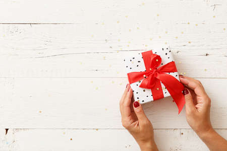 Top view of a gift tied with a red ribbon and wrapped in gift paper on a white wooden background covered with gold stars. Christmas, birthday or any other holiday preparations.