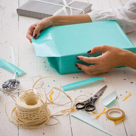 Close-up van de handen van een jonge vrouw die een feestelijk cadeau inpakken voor een verjaardag of voor een ander evenement. Linten, sterren, papier, schaar en een geschenk liggen op een witte houten tafel. ?oliday-concept Stockfoto