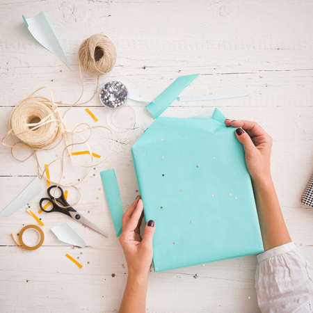 Close-up on a gift wrapped in paper of turquoise color. Hands of a young woman packing a gift on the background of a white wooden table. Preparations for the holiday Christmas, birthday, etc.