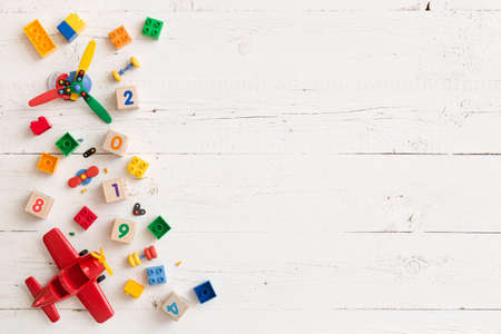 Multicolored plastic and wooden cubes with numbers scattered on a white wooden table. Top view of childrens toys and other equipment. Educational games for children. Cubes with numbers 2019.