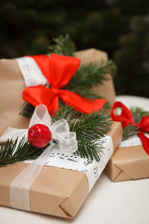 Closeup of gifts packaged in craft paper. Gifts for Christmas or New Year on the background of the Christmas tree. Festive season