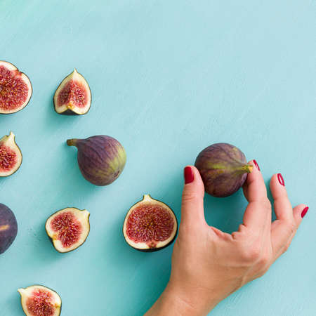 Closeup of fig fruits in the hand of a girl on the background of a wooden table. Top view of whole and sliced fig fruits on a blue background.