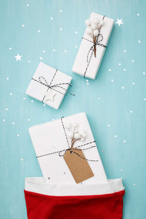 Closeup of stylish gifts for Christmas or New Year lying on a blue wooden background covered with silvery shining stars. Gifts from Santas hat. Festive concept