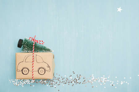 A car painted on a gift with a decorative tree tied to it is traveling along a path of stars on a BLUE background. A Christmas star shines in the sky. The concept of the holiday.