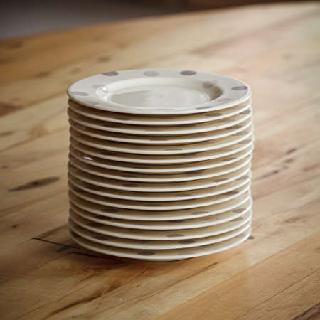 Closeup of plates on the table. A large stack of plates waiting for guests. Natural wooden table. House party. 스톡 콘텐츠