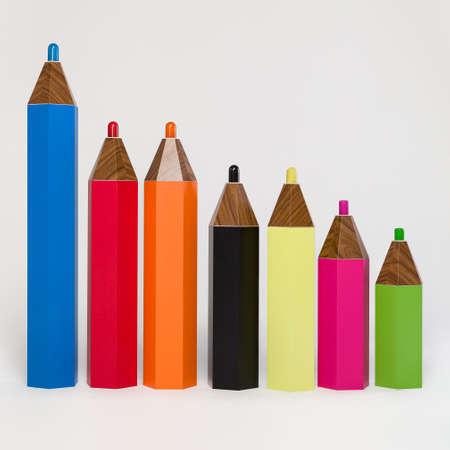 Photo of multi-colored pencils. Dummy handmade pencils stand on the floor in one line. Study and development.