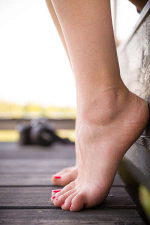 Closeup of the legs of a girl sitting on the veranda of her own home after a busy day. A young woman sitting on the porch stood on the fingers. Beautiful pedicure and feet.
