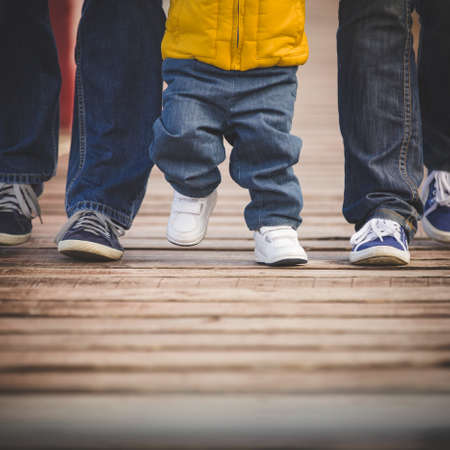 Closeup of legs walking along a wooden pier. Family, mom, dad and little son step on the wooden flooring. People in casual clothes and sneakers.