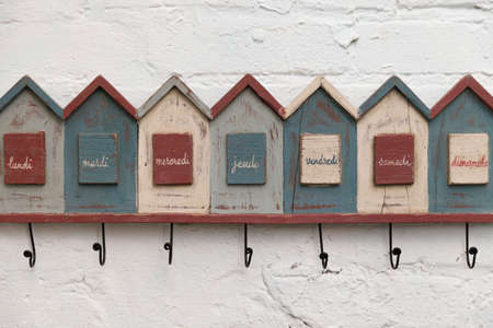Closeup wall hanger. Funny hanger in the form of houses with the signatures of the days of the week in French. Vintage coat hanger hanging on a white brick wall. 스톡 콘텐츠