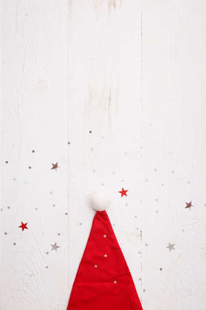 Top view of Santas red hat is lying on a white wooden table. Shining silver and red stars are scattered on the surface like snow. New year, Christmas, holiday concept