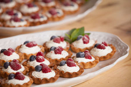Delicious homemade muffins with vanilla cream cheese and organic blueberries and raspberries on top. Healthy dessert for a celebration or party. Selective focus