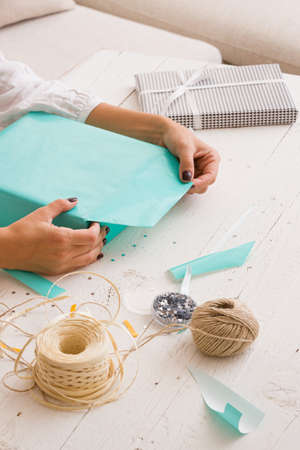 The hands of the girl wrapped a gift in a festive turquoise paper. Gift and accessories for packaging lie on a white wooden table. Birthday or other holidays concept 스톡 콘텐츠