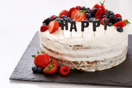 Closeup of a festive cake decorated with berries of strawberry, raspberry, blueberry. Candles the word HAPPY in the foreground. Layered cream cake on black board. Holiday and birthday party concept