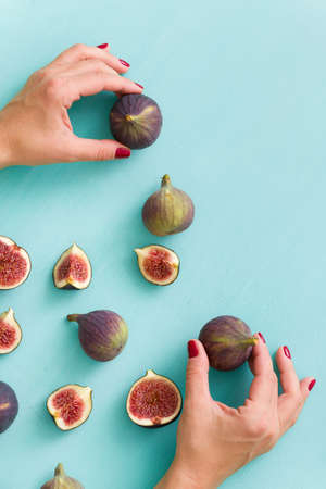 Closeup of hands of a young girl holding fresh fig fruits. Top view of figs lying on a blue wooden table.