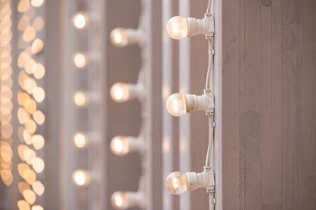 A burning garland of light bulbs on a vertical surface. Bulbs are chained, glow and create a festive mood. Bulbs for a holiday, party or wedding
