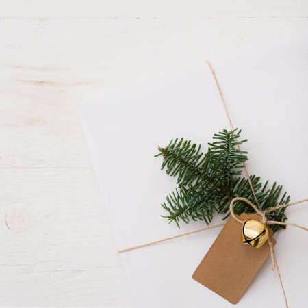 Closeup of a Christmas or New Years gift decorated with a bell, tag and fir branch. A gift wrapped in Christmas stylish paper lies on a white wooden table. Festive and Christmas concept 스톡 콘텐츠