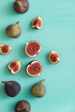 Top view of fig fruit scattered on a turquoise wooden table. Some figs are cut in half. 스톡 콘텐츠 - 130400816