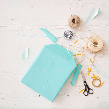 Closeup of a gift wrapped in turquoise color. Gift ribbons, twine, stars, scissors and a gift on a white wooden table. The concept of holiday, Christmas, birthday, etc. 스톡 콘텐츠 - 130400814