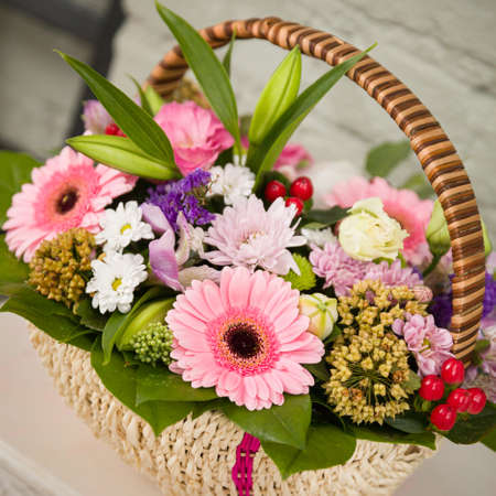 Top view of a beautiful basket with flowers. Chamomiles, gerberas and other exotic plants are gathered in a bouquet. Romantic mood. Holiday gift 스톡 콘텐츠 - 130400812