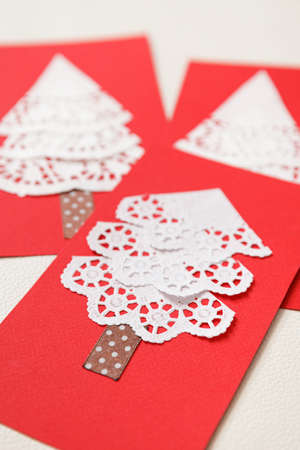 Beautiful cards made by hand with the help of improvised materials, napkins, red cardboard and packing tape. Cards for Christmas and New Year. Holiday concept 스톡 콘텐츠