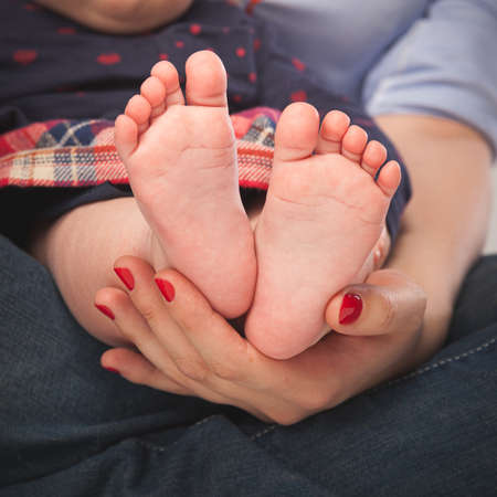 Closeup of the feet of a baby girl little girl in the arms of mom.