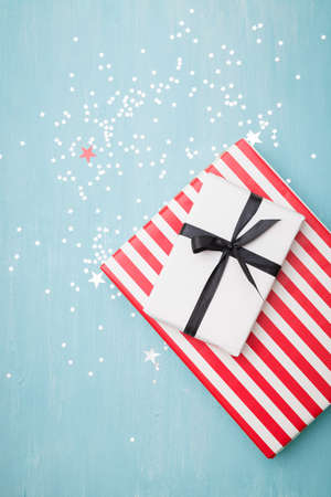 Top view of gifts lying on a blue wooden background. Stylish striped gift and a gift wrapped in white paper tied with a black ribbon. Silver stars are scattered on the table like confetti. 스톡 콘텐츠 - 130400945
