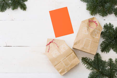 Stylish gifts for Christmas or New Year are packed in craft packages and decorated in the form of houses lying on a white wooden table surrounded by fir branches. Blank orange greeting card for text.