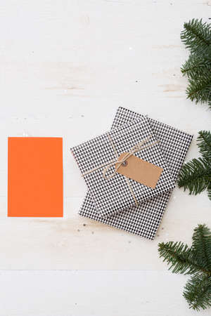 Stylishly packaged gifts with a tag and tied with a craft rope. Top view of the beautiful gifts for Christmas and New Year. Blank orange greeting card for text. Holiday season and winter concept