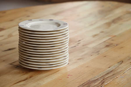 Closeup of a pile of plates standing on a wooden table. Preparing for the party and waiting for a large number of guests.