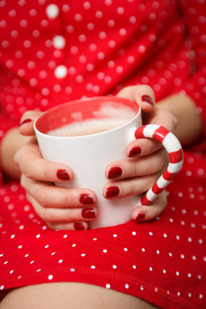 Closeup of hands of a young woman with a cup of coffee in her hands. Hands of a girl with a red manicure hold a white cup with cappuccino on the background of a red homemade polka dot dress. 스톡 콘텐츠