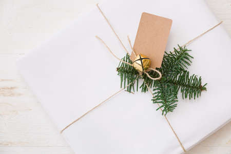 Closeup of a Christmas or New Years gift decorated with a spruce twig, tag and bell. A gift wrapped in white stylish paper lies on a white wooden table. Festive and Christmas concept
