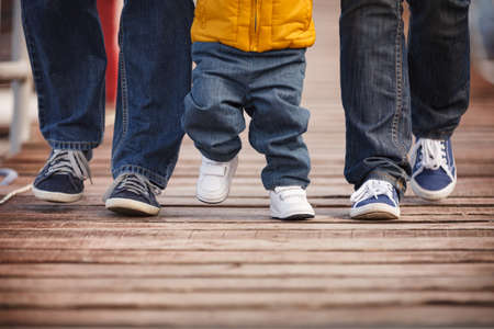Closeup of a family dressed in casual clothes walking along wooden flooring. Mom, dad and child step on a wooden pier on a cool autumn or spring day. 스톡 콘텐츠 - 130401055